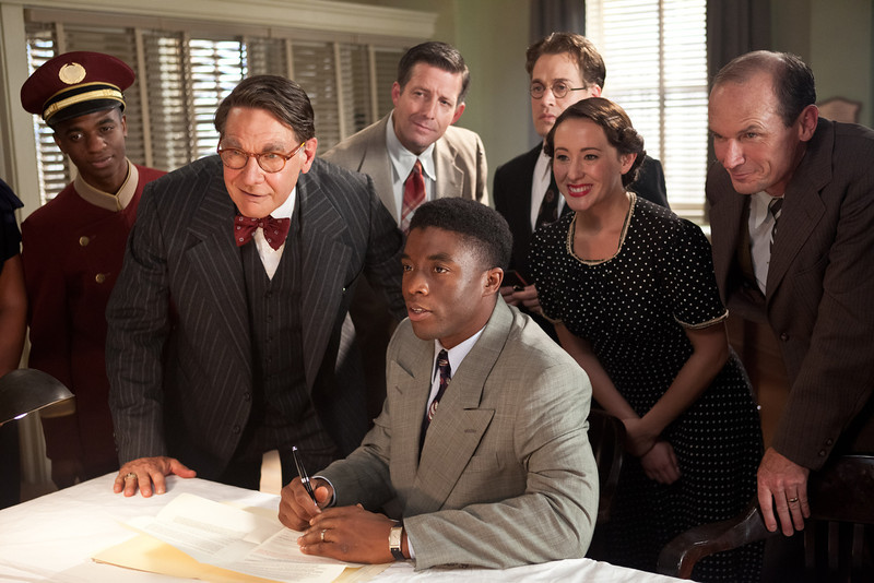 """. (Center l-r) HARRISON FORD as Branch Rickey and CHADWICK BOSEMAN as Jackie Robinson, T.R. KNIGHT (standing) as Harold Parrott, RHODA GRIFFIS as Miss Bishop and TOBY HUSS as Clyde Sukeforth in Warner Bros. Pictures� and Legendary Pictures� drama �\""""42\"""" a Warner Bros. Pictures release."""