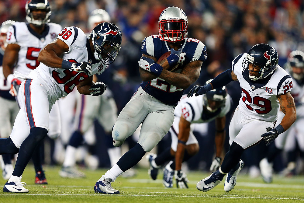 Description of . Stevan Ridley #22 of the New England Patriots runs with the ball against Danieal Manning #38 and Glover Quin #29 of the Houston Texans during the 2013 AFC Divisional Playoffs game at Gillette Stadium on January 13, 2013 in Foxboro, Massachusetts.  (Photo by Elsa/Getty Images)