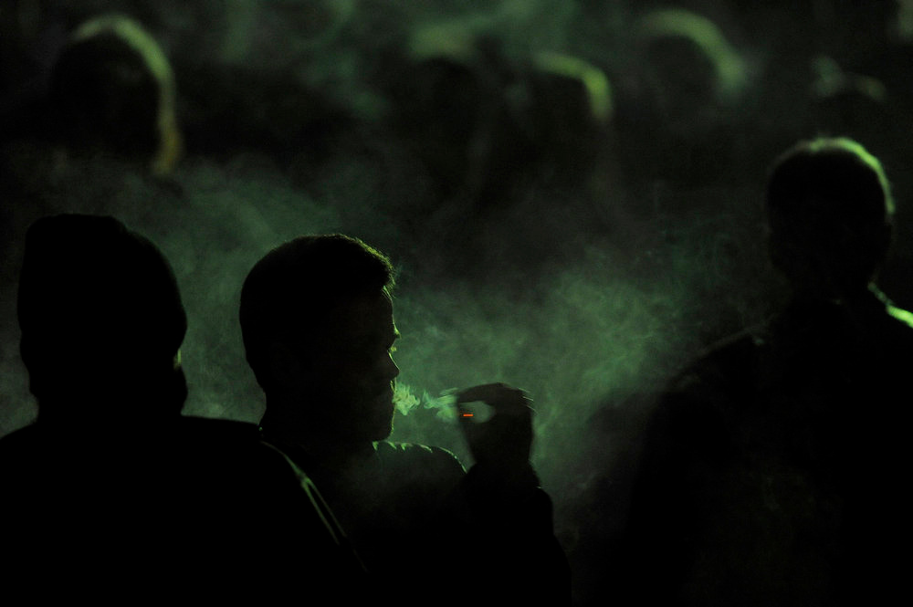 """. A man smokes a joint as he waits for Snoop Lion to take the stage for DJ set on Friday, April 19, 2013 at the Fillmore Auditorium in Denver. Snoop also presented his documentary Reincarnated at the first ever \""""Green Carpet\"""" event as a part of the High Times Cannabis Cup. Seth A. McConnell, The Denver Post"""