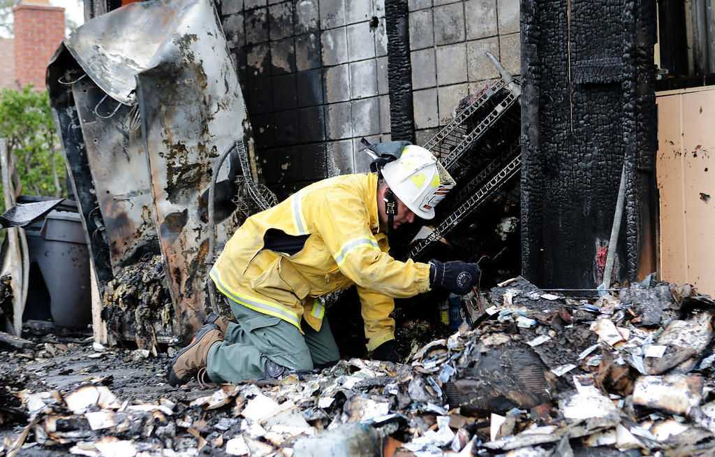 . Chief Dennis Johnsen, of the Santa Clara County Fire Department, searches the rubble for a cause of an early morning fire at the Happy Hound restaurant in Los Gatos, Calif. on Monday, March 4, 2013. The family owned restaurant has been a Los Gatos landmark for over forty years. (Gary Reyes/ Staff)