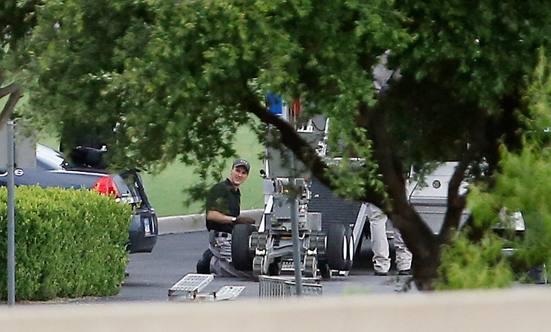 . Police appear to setup a remotely operated robot during a stand off with a gunman barricaded inside a van at a Jack in the Box restaurant at Interstate 45 and Dowdy Ferry Road, Saturday, June 13, 2015, in Hutchins, Texas. The gunman allegedly attacked Dallas Police Headquarters. (AP Photo/Brandon Wade)