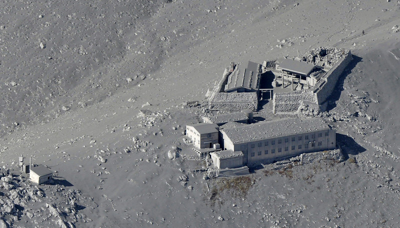 . Buildings of a mountain lodge near the summit crater are totally covered by ash spewed out by Mt. Ontake as the volcano erupts in central Japan Saturday, Sept. 27, 2014. Mt. Ontake erupted Saturday, sending a large plume of ash high into the sky and prompting a warning to climbers and others to avoid the area. Japanese broadcaster NHK, citing local authorities, said there were reports of injuries, but no word on their severity. (AP Photo/Kyodo News)