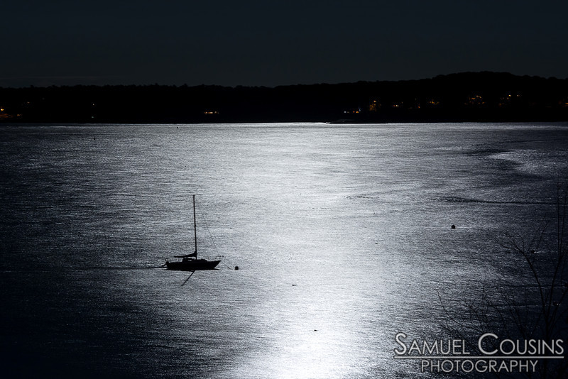 A small sailboat is moored in the reflected moonlight.