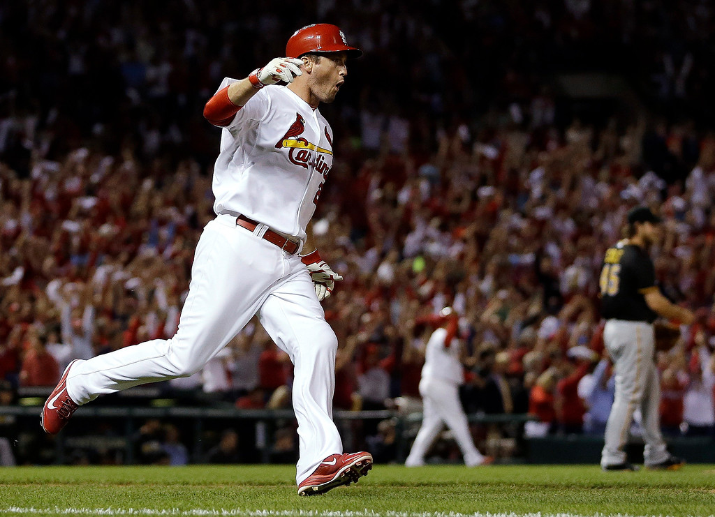 . St. Louis Cardinals\' David Freese runs to first base after hitting a two-run home run against Pittsburgh Pirates starting pitcher Gerrit Cole, right, in the second inning of Game 5 of a National League baseball division series, Wednesday, Oct. 9, 2013, in St. Louis. (AP Photo/Jeff Roberson)