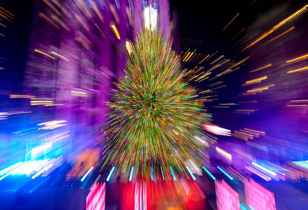 . The Rockefeller Center Christmas tree is lit   during a ceremony on Wednesday, Dec. 4, 2013 in New York. In this view, the lens was zoomed during the exposure. Some 45,000 energy efficient LED lights adorn the 76-foot tree. (Photo by Evan Agostini/Invision/AP)