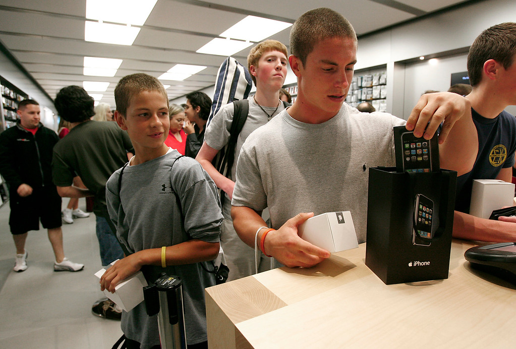 . Brothers Connor Sokolosky, left, and Taylor Sokolosky purchase the first Apple iPhones at this location, during the release of the Apple product and the opening of the new Apple Store at Woodland Hills Mall in Tulsa, Okla., on Friday, June 29, 2007. The brothers waited in line for 12 hours for the event and were first in line. (AP Photo/David Crenshaw)