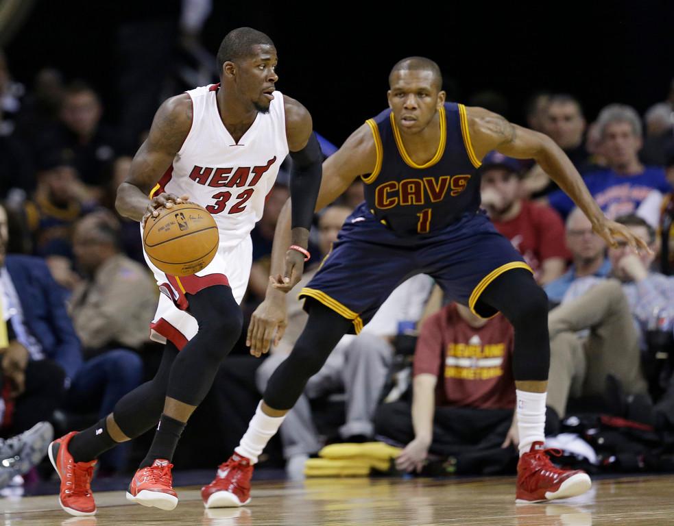 . Miami Heat�s James Ennis (32) drives past Cleveland Cavaliers\' James Jones (1) during an NBA basketball game Thursday, April 2, 2015, in Cleveland. (AP Photo/Tony Dejak)
