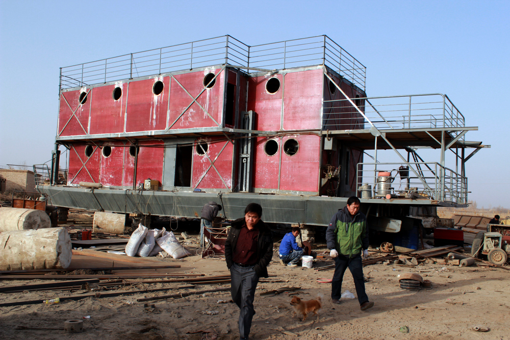 Description of . In this photo taken Nov. 24, 2012, Lu Zhenghai, right, walks near his ark-like vessel in China's northwest Xinjiang Uyghur Autonomous Region.  Lu Zhenghai is one of at least two men in China predicting a world-ending flood, come Dec. 21, the fateful day many believe the Maya set as the conclusion of their 5,125-year long-count calendar. Zhenghai has spent his life savings building the 70-foot-by-50-foot vessel powered by three diesel engines, according to state media. In Mexico's Mayan heartland, nobody is preparing for the end of the world; instead, they're bracing for a tsunami of spiritual visitors. (AP Photo/ANPF-Chen Jiansheng)