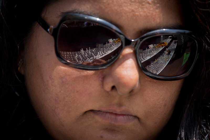 . A well-wisher lights a candle, seen reflected in her sunglasses, in memory of the victims of the Westgate Mall attack, outside the mall in Nairobi, Kenya Sunday, Sept. 21, 2014. Kenya is marking one year since four gunmen stormed the upscale Westgate Mall in Nairobi, killing 67 people, and a memorial plaque with the names of the victims was unveiled at a popular forest on the edge of the city. (AP Photo/Ben Curtis)