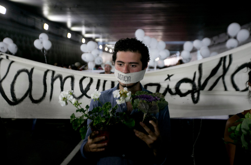 ". A student with his mouth covered with the word ""Justice\"" carries flowers during a protest marking the anniversary of the Tlatelolco massacre in Mexico City, Wednesday, Oct. 2, 2013. Mexico commemorated the 45th anniversary of the massacre of students holding an anti-government protest, killed by men with guns and soldiers in 1968 days before the Summer Olympics celebrations in Mexico City. (AP Photo/Eduardo Verdugo)"