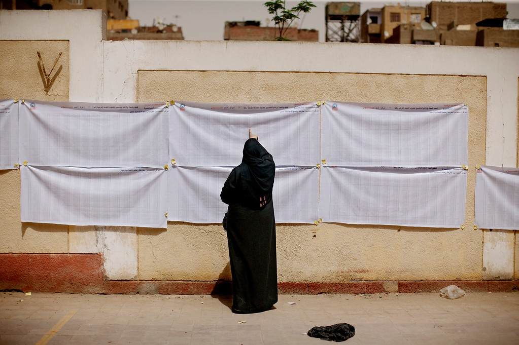 . In this May 23, 2012 file photo, an Egyptian woman searches for her name on a registration list outside a polling station in Helwan, a southern suburb of Cario, Egypt.  Egypt commenced two days of presidential voting after 16 months of interim rule by the Supreme Council of Armed Forces. This election was the first free and fair presidential race since the ouster of former President Hosni Mubarak.  (AP Photo/Pete Muller, File)