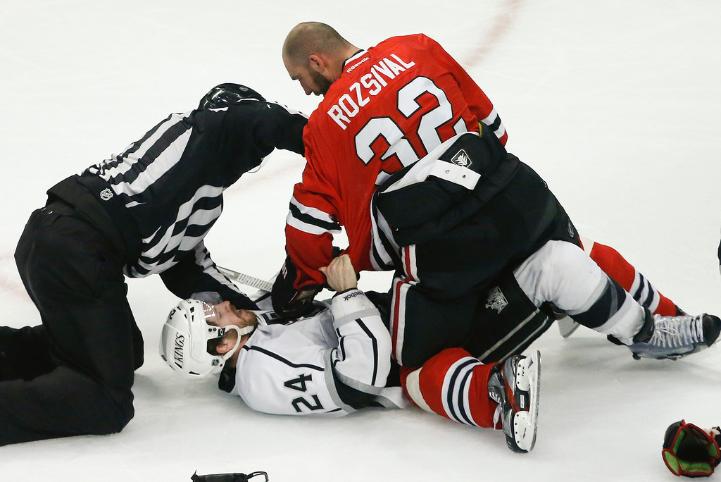 . The referee tries to break up a fight between Los Angeles Kings center Colin Fraser (24) and Chicago Blackhawks defenseman Michal Rozsival (32) during the third period in Game 2 of the NHL hockey Stanley Cup Western Conference finals Sunday, June 2, 2013 in Chicago. Chicago won 4-2. (AP Photo/Charles Rex Arbogast)
