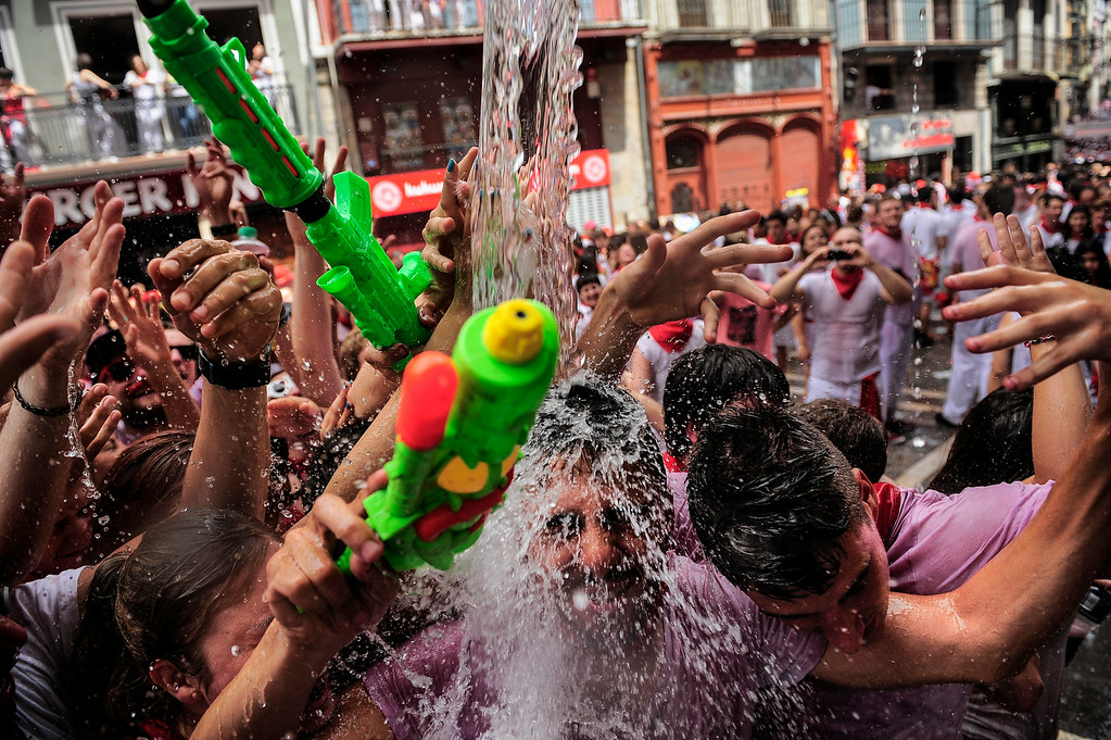 """. Revelers have water thrown on them from a balcony during the launch of the \'Chupinazo\' rocket, to celebrate the official opening of the 2014 San Fermin fiestas, in Pamplona, Spain, Sunday, July 6, 2014. Revelers from around the world kick off the festival with a messy party in the Pamplona town square, one day before the first of eight days of the running of the bulls glorified by Ernest Hemingway\'s 1926 novel \""""The Sun Also Rises.\"""" (AP Photo/Alvaro Barrientos)"""