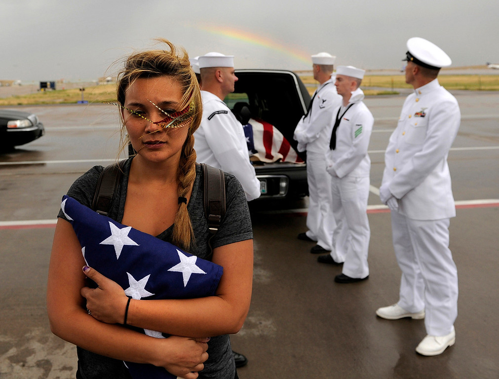 . Chantel Blunk, wife of Jonathan Blunk, waits on the tarmac at Denver International Airport as her husband\'s body is prepared to be flown to Reno, Nevada for his full military funeral. Blunk, a five-year U.S. Navy veteran, was killed when James Holmes opened fire at a crowded movie theater. RJ Sangosti, The Denver Post