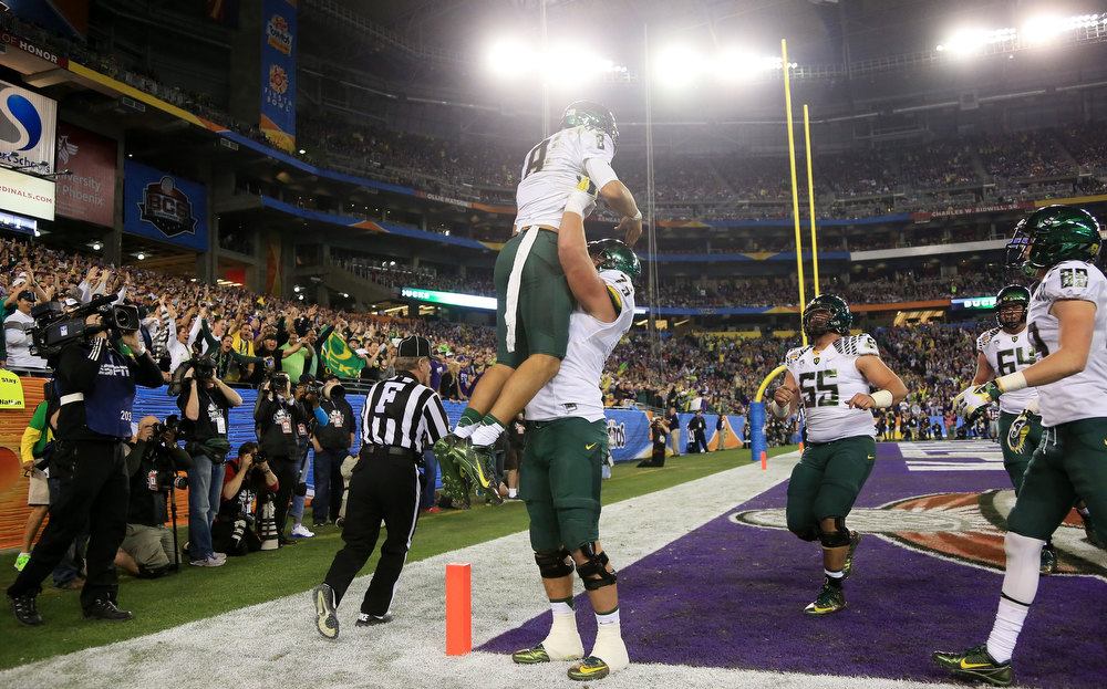 Description of . Marcus Mariota #8 celebrates his third quarter touchdown with Jake Fisher #75 of the Oregon Ducks during the Tostitos Fiesta Bowl against the Kansas State Wildcats at University of Phoenix Stadium on January 3, 2013 in Glendale, Arizona.  (Photo by Doug Pensinger/Getty Images)