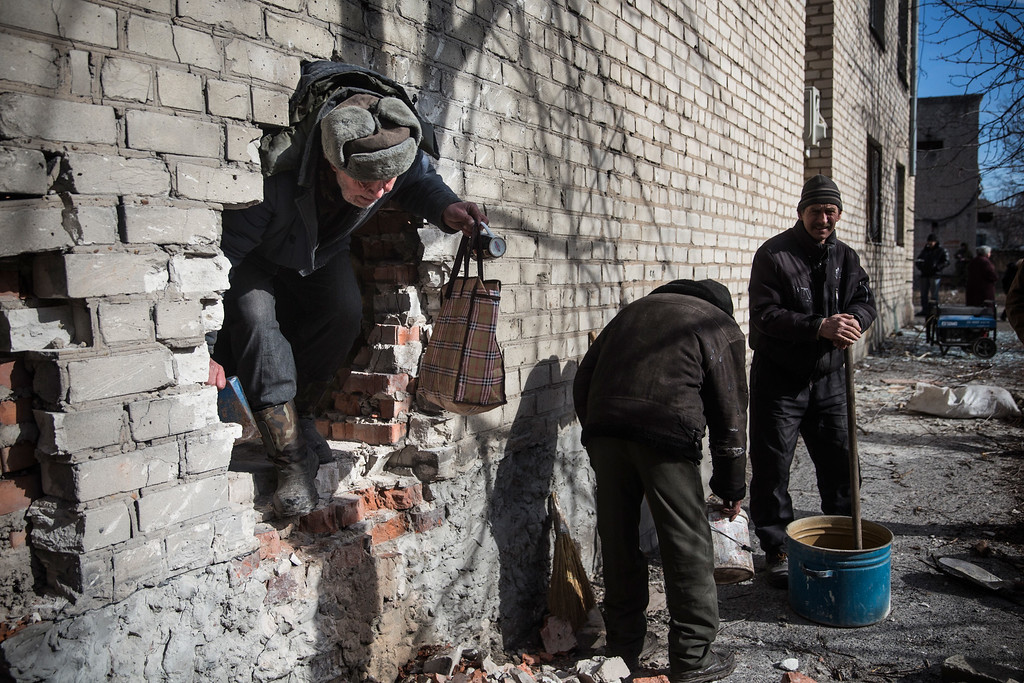 . DEBALTSEVE, UKRAINE - FEBRUARY 25:  Men use bricks and mortar to repair a hole blown in the side of a bank during heavy fighting on February 25, 2015 in Debaltseve, Ukraine. After approximately one month of fighting, Russian backed rebels successfully forced Ukrainian troops to withdraw from the town on February 18. The town is considered an asset to both Ukrainians and the rebels due to the railway station and it\'s connection to other eastern Ukranian towns.  (Photo by Andrew Burton/Getty Images)