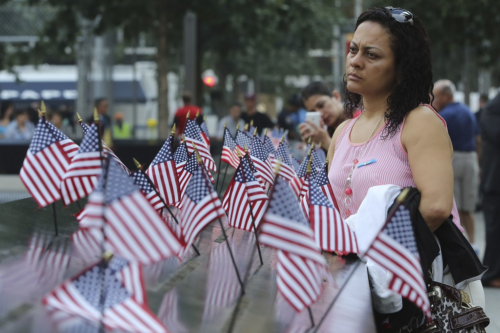 . A mourner pauses at the south reflecting pool of the 9/11 Memorial during a ceremony marking the 12th anniversary of the 9/11 attacks on the World Trade Center in New York, on September 11, 2013.  AFP PHOTO/POOL/Mary  ALTAFFER/AFP/Getty Images
