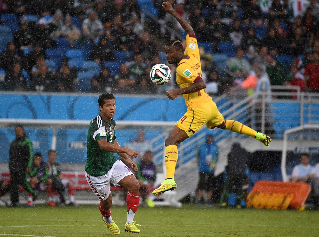 . Mexico\'s forward Giovani Dos Santos (L) fights for the ball with Cameroon\'s defender Aurelien Chedjou during a Group A football match between Mexico and Cameroon at the Dunas Arena in Natal during the 2014 FIFA World Cup on June 13, 2014. AFP PHOTO / CHRISTOPHE SIMON/AFP/Getty Images