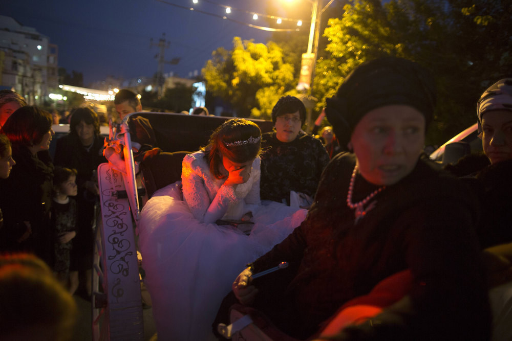 Description of . A Jewish bride is accompanied by relatives in a horse-drawn carriage during the wedding of the great-grandson of the Rabbi of the Tzanz Ultra-Orthodox Hasidic community in Netanya, on January 1, 2013. MENAHEM KAHANA/AFP/Getty Images