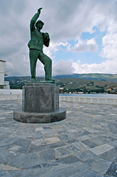 """The marble-paved Riva Square, that we reached by walking through the old Andros Town, (also known as Chora). This is the  copper statue of the """"Unknown Sailor"""", by Michael Tombros. It is dedicated to all those lost at sea serving in Greece's Merchant Shipping Companies. Andros has strong sea-going links and used to be known as """"The Island of Captains""""  OM4T Z. 21 F2 at f11  Kod 100 Ektar"""