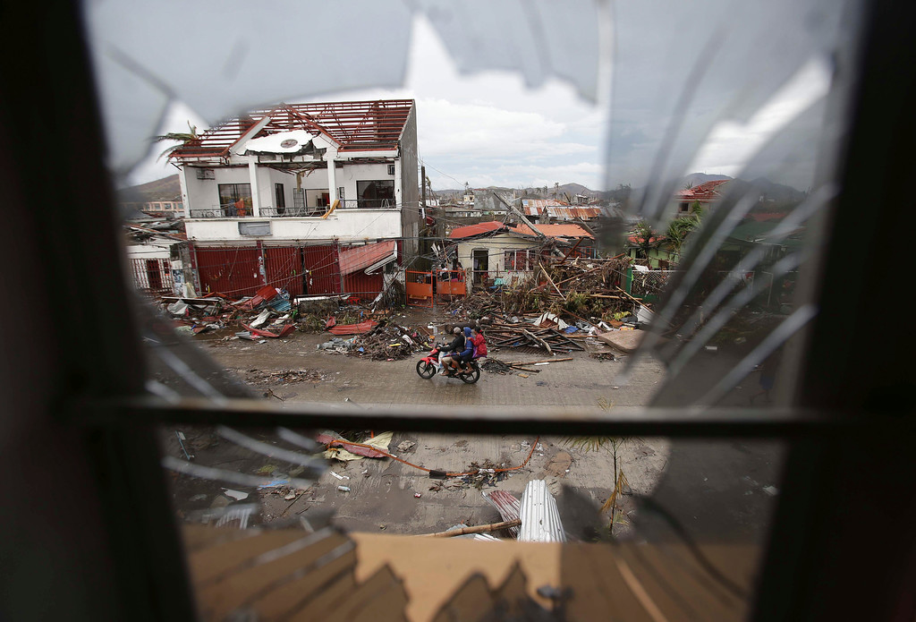 . Damaged homes are seen through a broken window after strong winds from Typhoon Haiyan tore down houses at Tacloban city, Leyte province, central Philippines on Tuesday, Nov. 12, 2013. Four days after Typhoon Haiyan struck the eastern Philippines, assistance is only just beginning to arrive. (AP Photo/Aaron Favila)