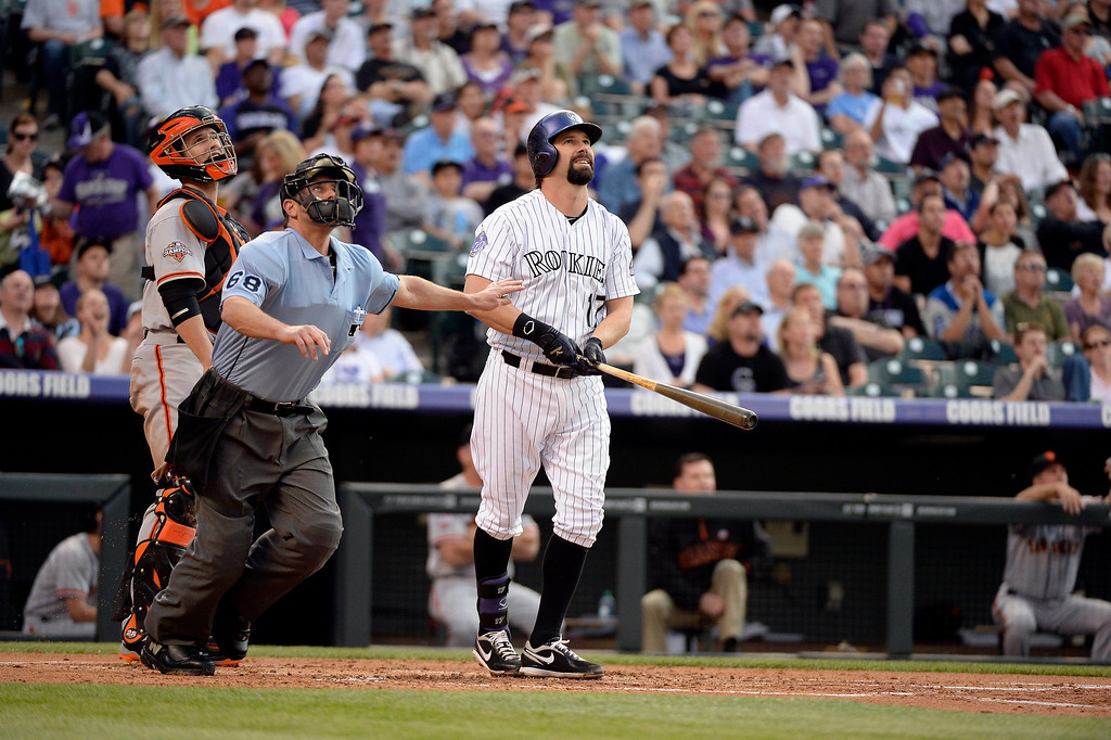 . Buster Posey (28) of the San Francisco Giants, HP Chris Guccione and Todd Helton (17) of the Colorado Rockies watch to see if the ball is fair down the line. Todd hits a two run home run off of Matt Cain (18) of the San Francisco Giants during the second inning May 16, 2013 at Coors Field. (Photo By John Leyba/The Denver Post)