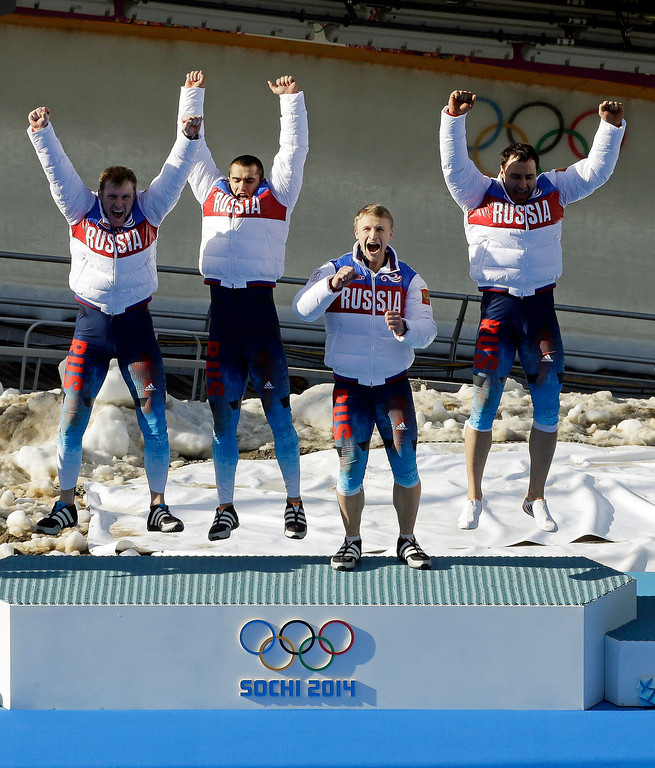 . The team from Russia RUS-1, with Alexander Zubkov, Alexey Negodaylo, Dmitry Trunenkov, and Alexey Voevoda, jump onto the medal stand after they won the gold medal during the men\'s four-man bobsled competition final at the 2014 Winter Olympics, Sunday, Feb. 23, 2014, in Krasnaya Polyana, Russia.  (AP Photo/Dita Alangkara)
