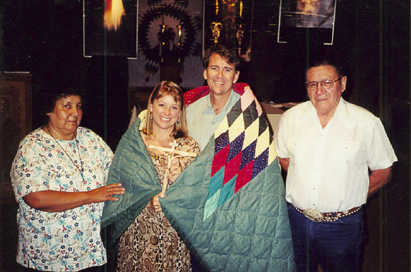 At the beginning of our apostolate on one of our very first missions to an Indian reservation, Deacon and his wife present us with a hand made quilt and adopt us into their family as they wrap it around us