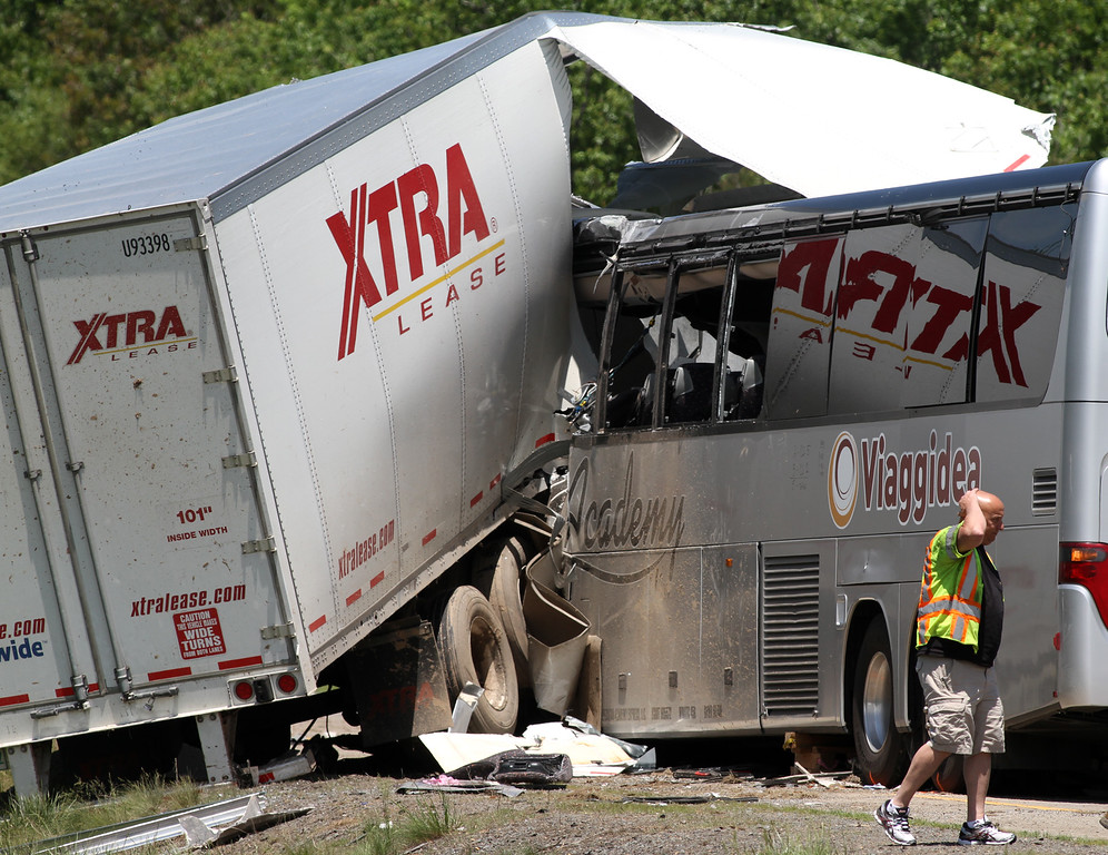 . A man walks near the scene of a fatal collision between a tractor-trailer and a tour bus on Interstate 380 near Tobyhanna, Pa., Wednesday, June 3, 2015. Multiple people were killed and more than a dozen were sent to hospitals. (Jake Danna Stevens/The Times & Tribune via AP)