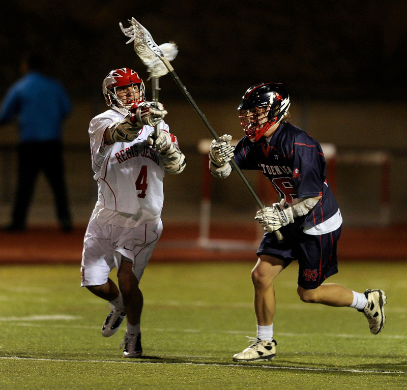 . AURORA, CO. - APRIL 24:  Raiders sophomore Chet Dunstan (4) tried to knock the ball from the stick of Kent Denver defenseman Jack Ammons (16) in the second half. The Regis Jesuit High School boy\'s lacrosse team defeated Kent Denver 10-8 Wednesday night, April 24, 2013. Photo By Karl Gehring/The Denver Post