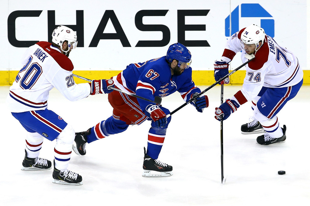 . Benoit Pouliot #67 of the New York Rangers hits Alexei Emelin #74 of the Montreal Canadiens in the face with his stick in the first period during Game Four of the Eastern Conference Final in the 2014 NHL Stanley Cup Playoffs at Madison Square Garden on May 25, 2014 in New York City.  (Photo by Al Bello/Getty Images)