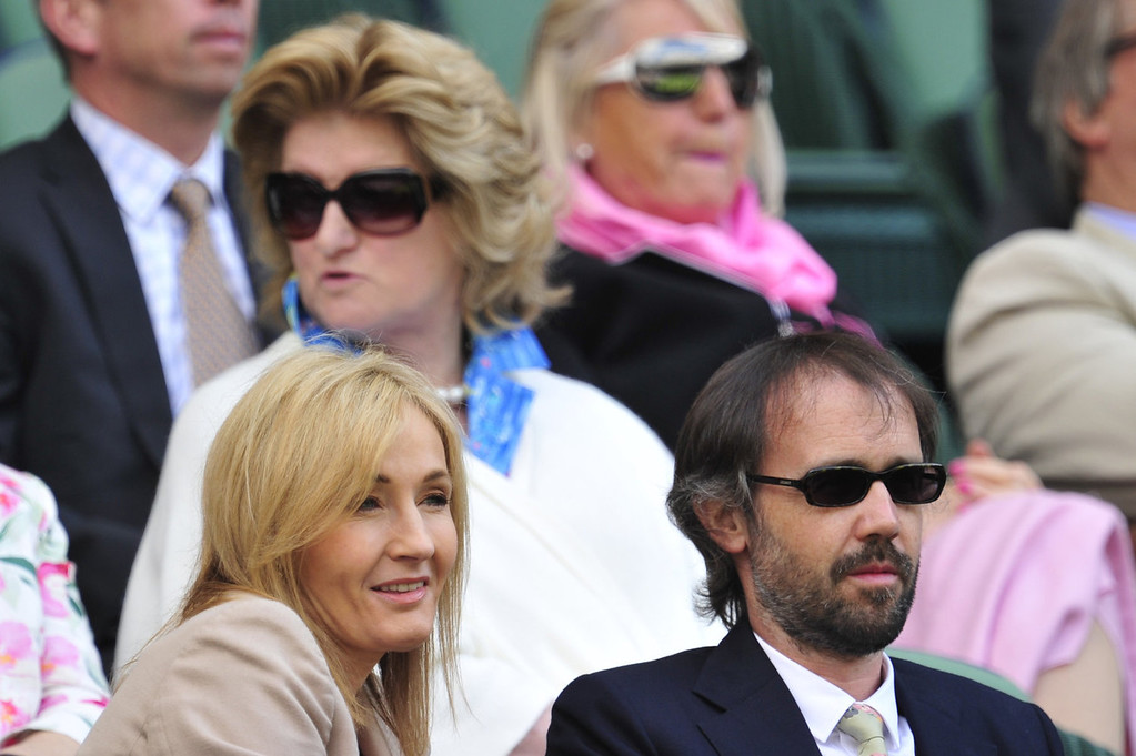 . British author J K Rowling (L) sits watching the action on centre court with her husband Neil Murray (R) during play on day two of the 2013 Wimbledon Championships tennis tournament at the All England Club in Wimbledon, southwest London, on June 25, 2013.  GLYN KIRK/AFP/Getty Images