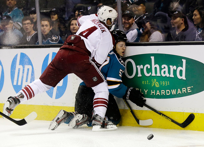 . San Jose Sharks center Tommy Wingels, right, is pressed up against the boards by Phoenix Coyotes defenseman Zbynek Michalek, of the Czech Republic, during the first period of an NHL hockey game in San Jose, Calif., Thursday, Jan. 24, 2013. (AP Photo/Marcio Jose Sanchez)