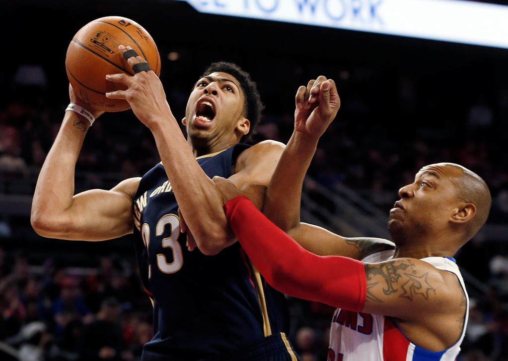 . New Orleans Pelicans forward Anthony Davis (23) is fouled by Detroit Pistons forward Caron Butler during the second half of an NBA basketball game in Auburn Hills, Mich., Wednesday, Jan. 14, 2015. (AP Photo/Paul Sancya)