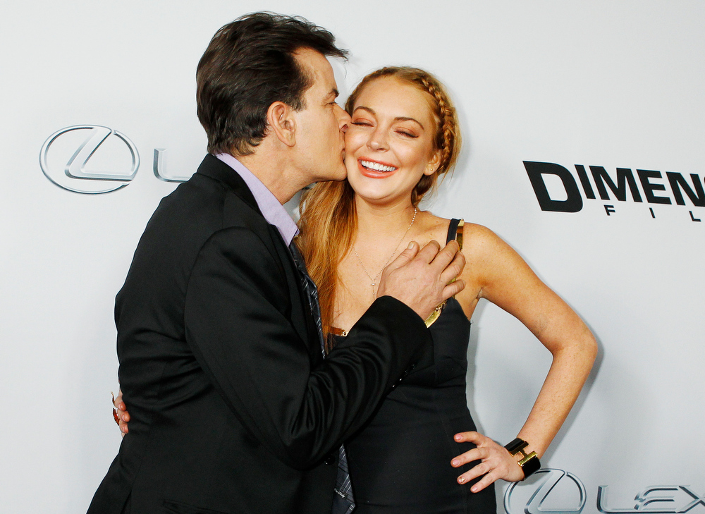 """. Cast member Charlie Sheen kisses co-star Lindsay Lohan on the cheek as they pose at the premiere of their new movie \""""Scary Movie 5\"""" in Hollywood April 11, 2013.  REUTERS/Fred Prouser"""