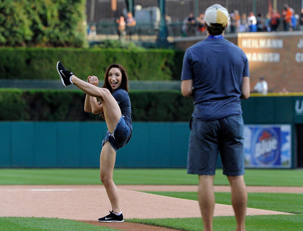 . Ice dance gold medalist Meryl Davis, left, prepares to pitch to her dance partner, Charlie White, before a baseball game between the Detroit Tigers and the San Francisco Giants on Friday, Sept. 5, 2014, in Detroit. (AP Photo/Jose Juarez)
