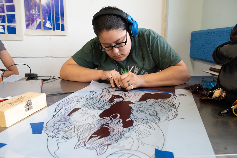 Erika Max cuts away tiny pieces of her screen print design for Professor Ryan O'Malley's Advanced Printmaking course.