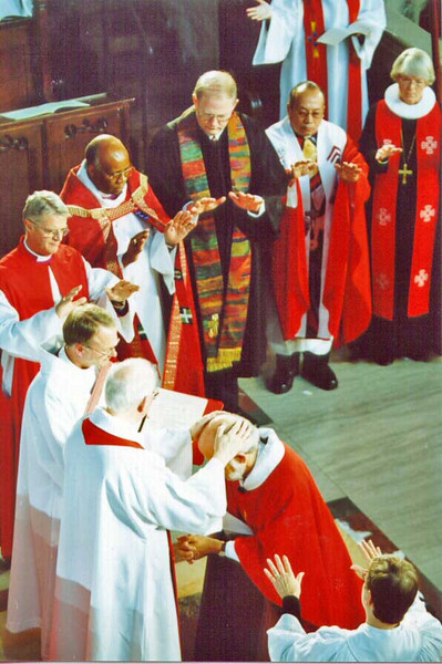 Bishop Anderson, left front, installs Bishop-Elect Hanson, kneeling. ELCA ecumenical partners and Lutheran bishops from other continents, symbolically extend their hands. Each also placed their hands on Hanson's head during the installation.