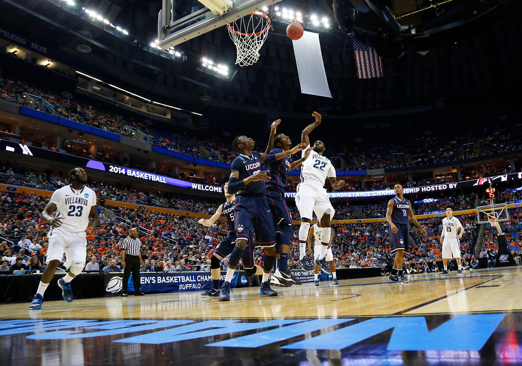 . Villanova\'s JayVaughn Pinkston (22) shoots over Connecticut\'s DeAndre Daniels and Amida Brimah (35) during the first half of a third-round game in the NCAA men\'s college basketball tournament in Buffalo, N.Y., Saturday, March 22, 2014. (AP Photo/Bill Wippert)