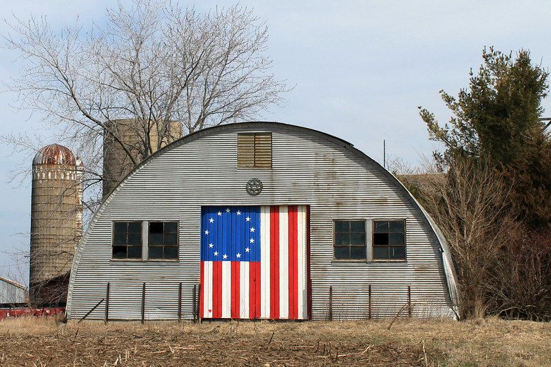 """Quonset Hut on the Prairie"" - Daily Photo - 05/18/13  Having spent some time in Quonset Huts while in the Marine Corps., this building held some nostalgia for me.  Nice to see it put to use.  You may remember these from World War II photos, films in the 1950s or Gomer Pyle.  Surprised to see an organization formed focused on these structures and the hyperbole is a little over the top, though they are trying to sell a book.  Hope you enjoy!   http://www.quonsethuts.org/index.htm  The Book:   Quonset Hut: Metal Living For A Modern Age tells the story of this unique architectural phenomena, from its birth during WWII as a mass-production shelter to its new status as an icon of American pragmatism, ingenuity, perseverance, and individuality.  When World War II came along, the American military found itself in need of a prefabricated, lightweight shelter that could be easily shipped and quickly assembled. The Quonset hut, that sliced tube of corrugated metal, was the answer. More than 153,000 were produced as part of the war effort. In its aftermath, even more were built and existing huts were adapted to house the postwar population boom. Of course, it couldn't last: the American desire for permanence meant decay and neglect for many of these rough-and-ready shelters and quickie warehouses.  But in the midst of its almost tragic tale of extinction, the Quonset hut has emerged as an unexpected icon of Americana and an oasis of architectural imagination. Travel the back roads of America and you will find the Quonset's distinctive shape enclosing everything from houses of worship to houses of pancakes.  Quonset Hut tells the story of this unique architectural phenomena, from its birth during WWII as a mass-production shelter to its new status as an icon of American pragmatism, ingenuity, perseverance, and individuality."