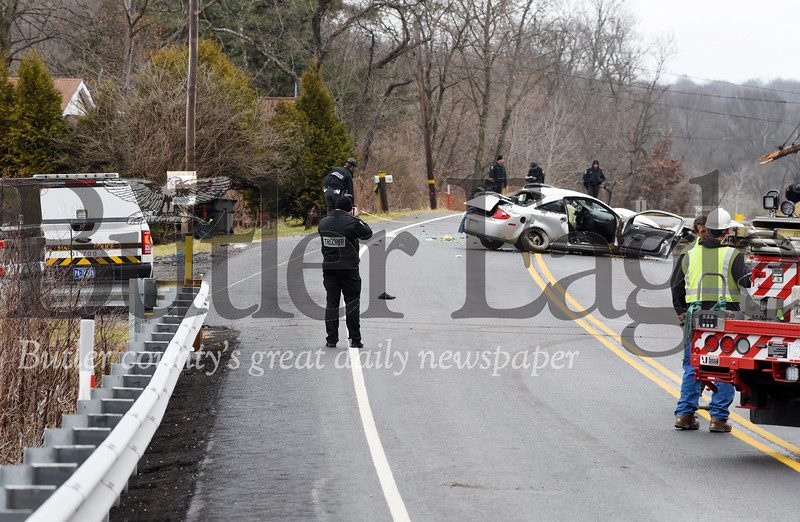 Harold Aughton/Butler Eagle: A PSP forensic trooper takes photos of  a car that struck a utility poll along route 38 Tuesday, Dec. 10, 2019.