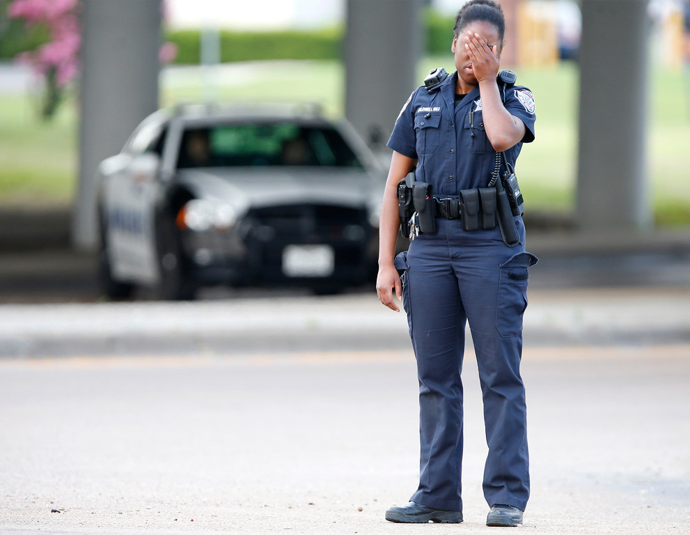. A fatigued deputy with the Dallas Sheriff\'s Department redirects traffic from an intersection near the scene of a standoff between police and a single gunman on June 13, 2015 in Hutchins, Texas. A lone shooter in an armored van, believed to be rigged with explosives, opened fire on the Dallas Police Headquarters early Saturday morning. The shooter reportedly unleashed multiple rounds and planted explosive devices around the station before leading police on a chase that ended in a standoff in the parking lot of a fast food restaurant. (Photo by Stewart F. House/Getty Images)