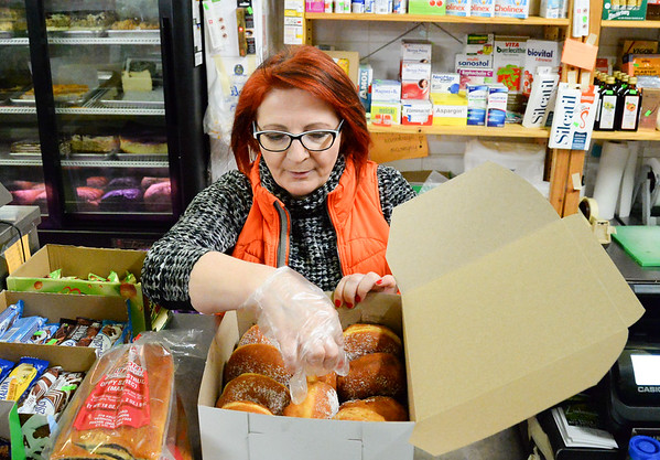 02/28/19 Wesley Bunnell | Staff Zieleniak Deli co owner Beata Rulka puts together a box of paczki for a customer on Fat Thursday.