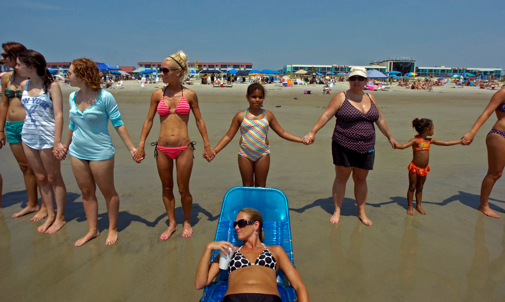 . People hold hands during a Hands Across the Sand event in Tybee Island, Ga., on June 26, 2010, about two months after the explosion of the Deepwater Horizon oil rig in the Gulf of Mexico. A high-stakes trial to assign blame and help figure out exactly how much more BP and other companies should pay for the spill began Monday, Feb. 25, 2013. (AP Photo/Stephen Morton, File)
