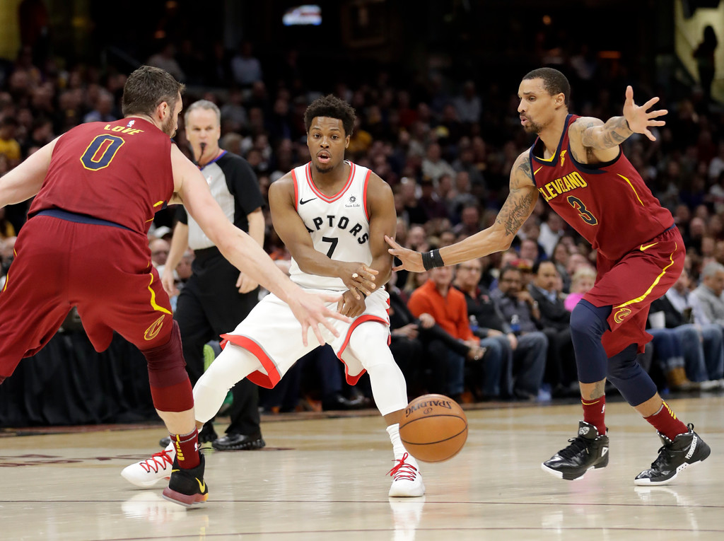 . Toronto Raptors\' Kyle Lowry (7) passes the ball between Cleveland Cavaliers\' Kevin Love (0) and George Hill (3) during the first half of an NBA basketball game Wednesday, March 21, 2018, in Cleveland. (AP Photo/Tony Dejak)