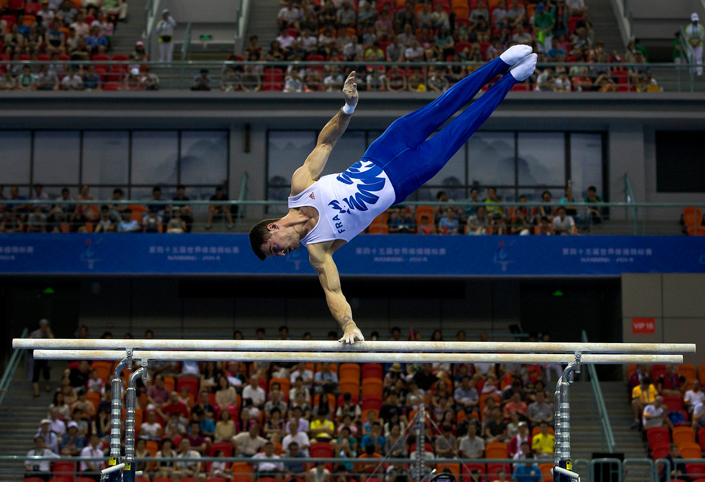 . Jim Zona of France competes on the parallel bars during the Artistic Gymnastics World Championships at the Guangxi Gymnasium in Nanning, capital of southwest China\'s Guangxi Zhuang Autonomous Region Saturday, Oct. 4, 2014. (AP Photo/Andy Wong)