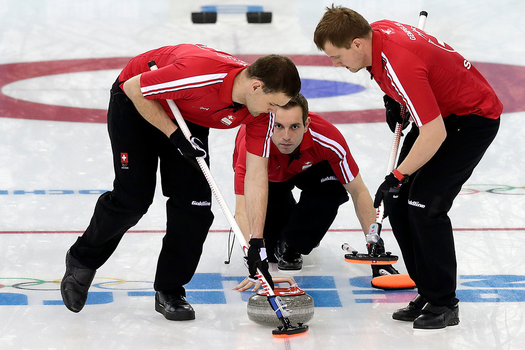 . Switzerland\'s skip Michel Sven, center, watches as Sandro Trolliet, left, and Simon Gempeler right, sweep the ice during the men\'s curling competition at the 2014 Winter Olympics, Wednesday, Feb. 12, 2014, in Sochi, Russia. (AP Photo/Wong Maye-E)