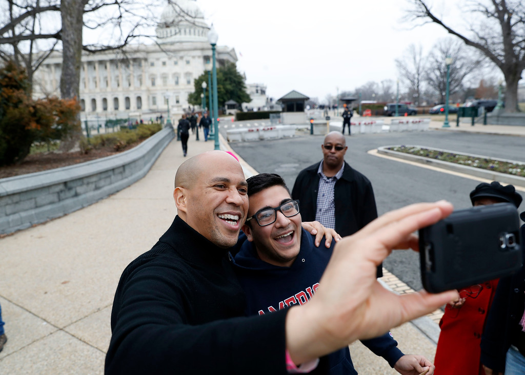 . Sen. Cory Booker, D-N.J., left, takes a selfie with Abbas Iseahany, from Tenafly, N.J., an American University student, during the Women\'s March on Washington, Saturday, Jan. 21, 2017 in Washington. (AP Photo/Alex Brandon)