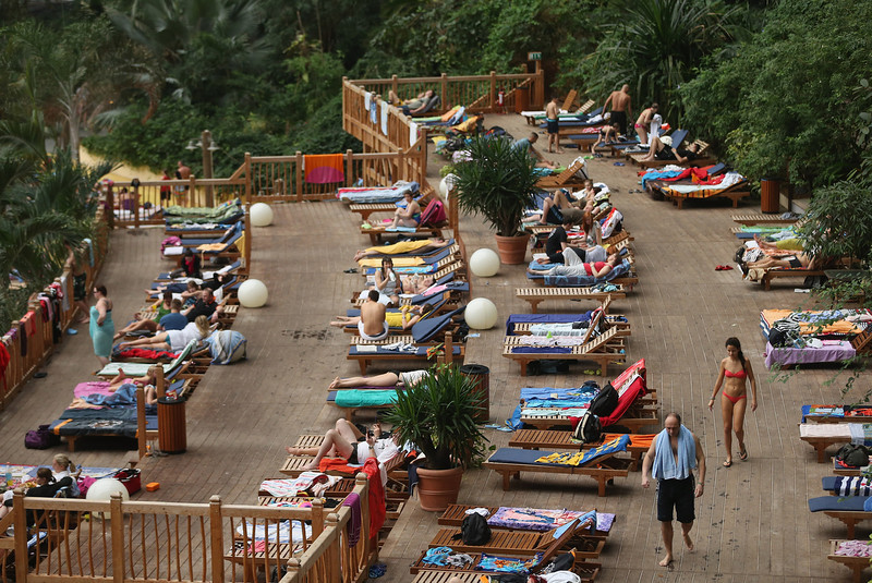 ". Visitors lounge on a deck that overlooks the ""South Sea\"" beach at the Tropical Islands indoor resort on February 15, 2013 in Krausnick, Germany. Located on the site of a former Soviet military air base, the resort occupies a hangar built originally to house airships designed to haul long-distance cargo. Tropical Islands opened to the public in 2004 and offers visitors a tropical getaway complete with exotic flora and fauna, a beach, lagoon, restaurants, water slide, evening shows, sauna, adventure park and overnights stays ranging from rudimentary to luxury. The hangar, which is 360 metres long, 210 metres wide and 107 metres high, is tall enough to enclose the Statue of Liberty.  (Photo by Sean Gallup/Getty Images)"