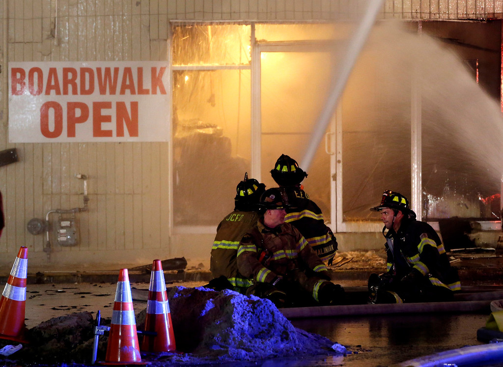 . Firefighters sit on a hose while battling a blaze in a building on the Seaside Park boardwalk on Thursday, Sept. 12, 2013, in Seaside Park, N.J. The fire began in a frozen custard stand on the Seaside Park section of the boardwalk and quickly spread north into neighboring Seaside Heights. (AP Photo/Julio Cortez)